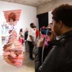 A visitor takes a photo of artwork by Karen Navarro at the Slowed and Throwed opening reception. Photo by Tere Garcia, 2020.